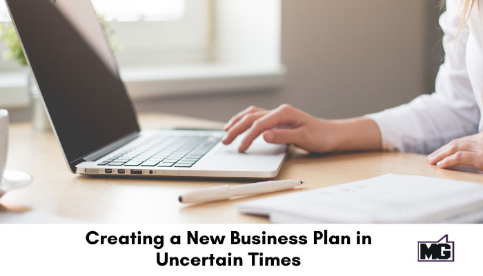Creating a new business plan with a laptop and notebook.